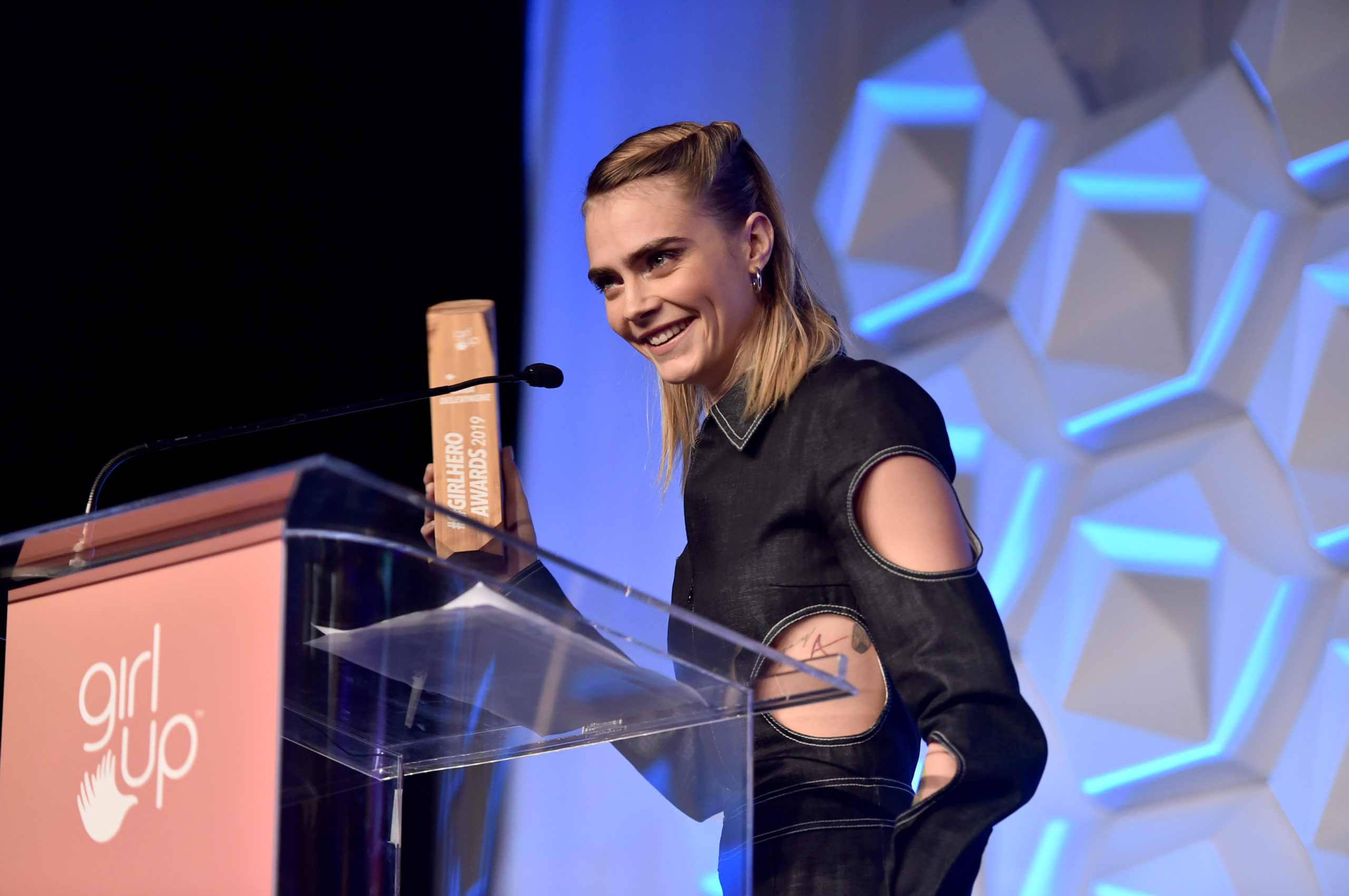 (close shot ) Cara Delevingne is holding her award next to the podium, and smile to the crowd